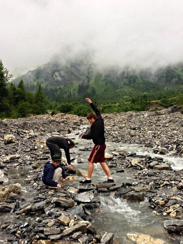 boys playing with river stones in adelboden