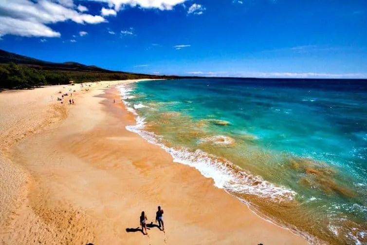 couple walking on beach in maui