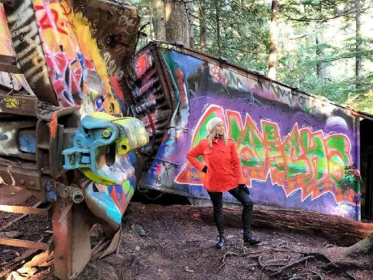 lady in orange coat in front graffiti covered train wreck in whistler