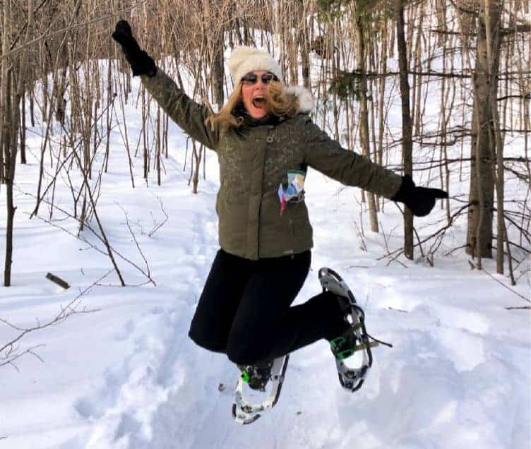 lady jumping with snowshoes in winter