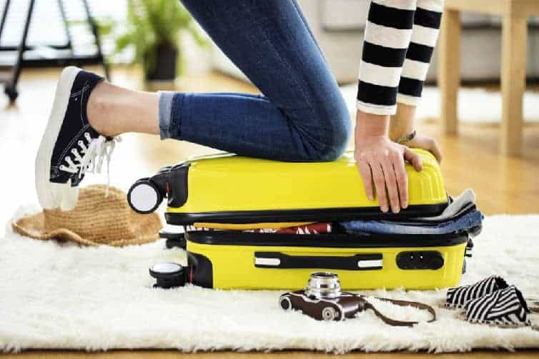 lady kneeling on suitcase to pack items for trip