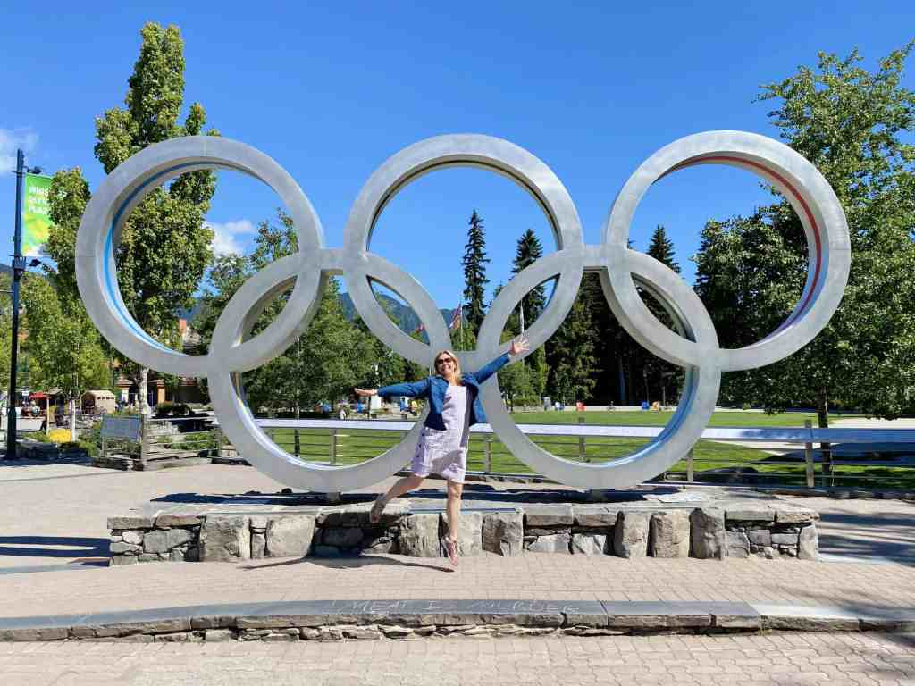woman jumping in whistler olympic plaza in summer