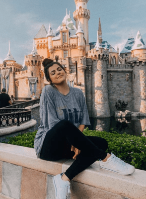 brunette girl smiling in front of a castle