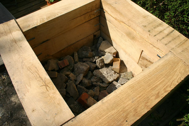 Plinth part-filled with rubble showing internal structure and angle brackets.