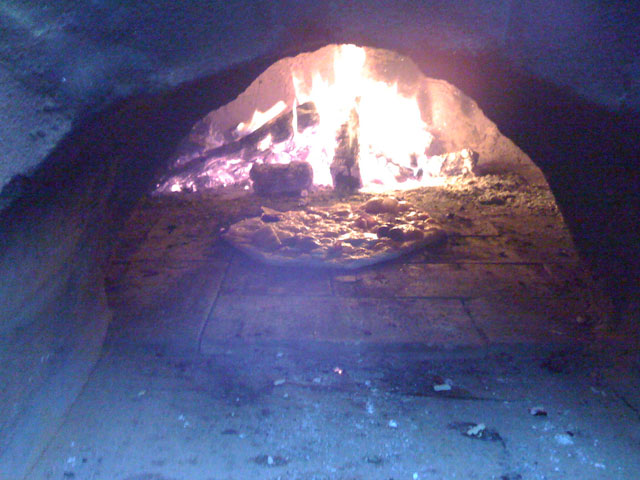Pizza cooking with fire burning ar rear.