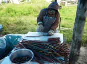 Yupiq woman preparing smoked king salmon strips for storage