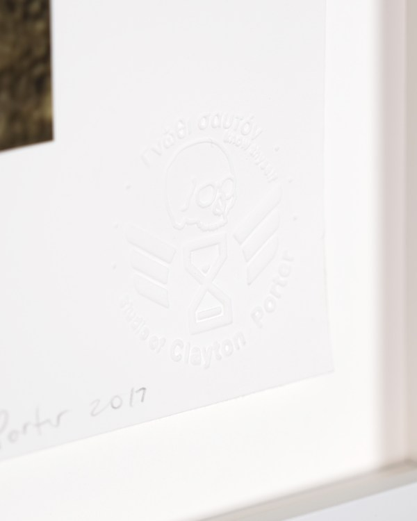 Embossed stamp on rag paper with the image of a human skull above a hourglass with wings with the Greek text know thyself above and studio of Clayton Porter below.
