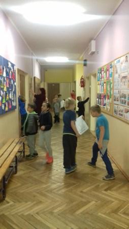 Rozwieszanie plakaów na szkolnym korytarzu