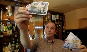A barman holding Scottish pound notes in a pub in London