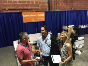 Rod Richardson and Elizabeth Halliday speak to one of the 175,000 guests at EarthX 2019 in Dallas in the Centennial Building, Clean Capitalist Coalition Networking Lounge