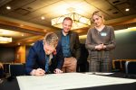 Chris Barnard of the British Conservation Alliance signs The Declaration on Energy Choice & Competition as Richard Lorenc, Foundation for Economic Education, and Marina Dolgova, American Conservation Coalition, look on.
