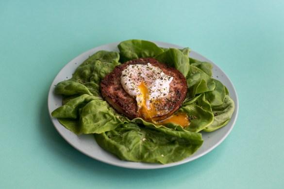 Käsleberkäse mit pochiertem Ei auf grünen Salat