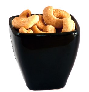 Black bowl with cashew nuts isolated on white background