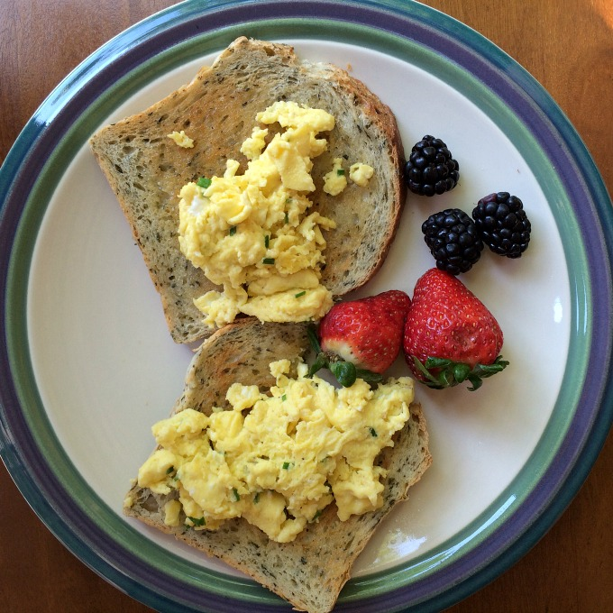 His Scrambled Eggs with Chives, Rye Bread and Berries