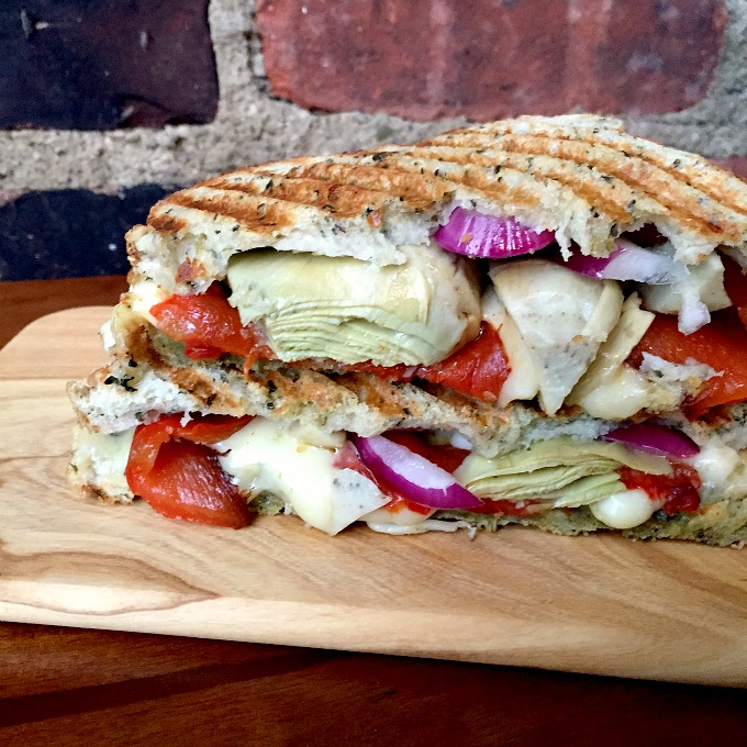 This sandwich, packed with pesto, mozzarella, artichoke hearts, red onion, and roasted red bell peppers, makes for The Ultimate Italian Panini.