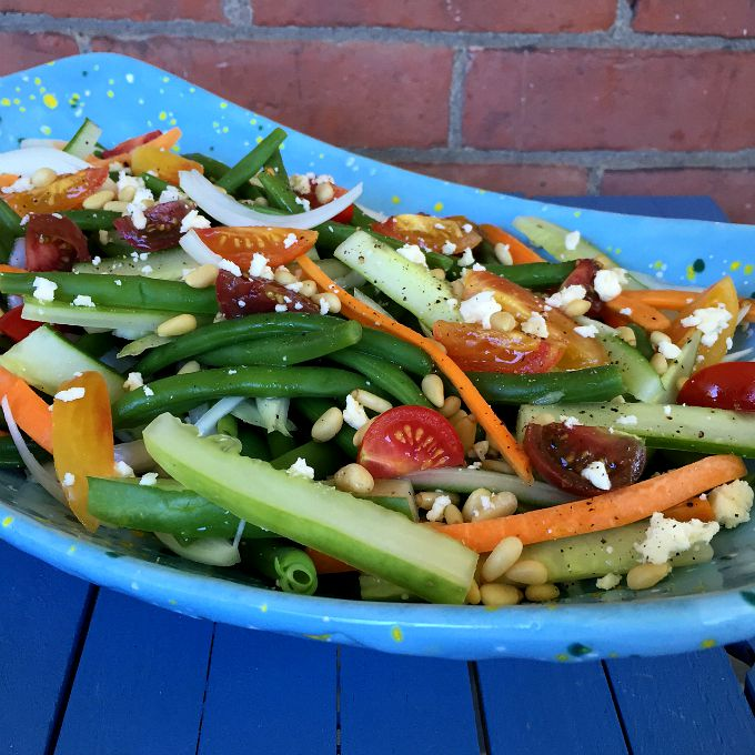 A Cool and Healthy Green Bean Salad with All the Toppings: Carrots, Cucumbers, Onions, Tomatoes, Pine Nuts and Feta. These are not yo' mama's green beans.