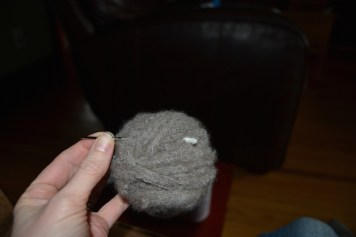 Pull the needle through the ball with the yarn