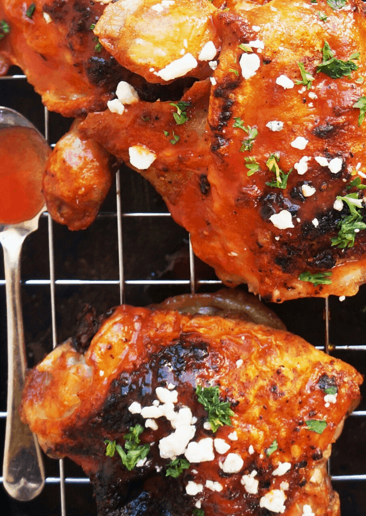 baked chicken thighs with spoonful of buffalo sauce on wire rack