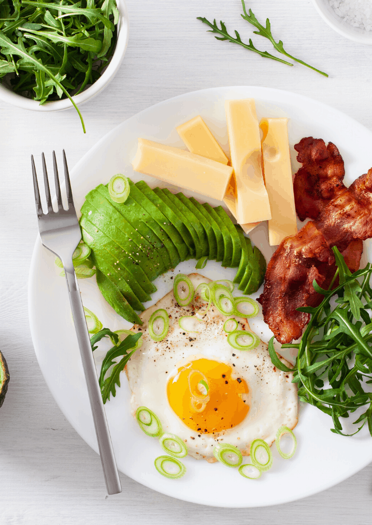 plate with fried egg, sliced avocado, and bacon