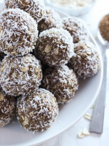 45 degree close-up view of stacked chocolate coconut peanut butter balls on white plate