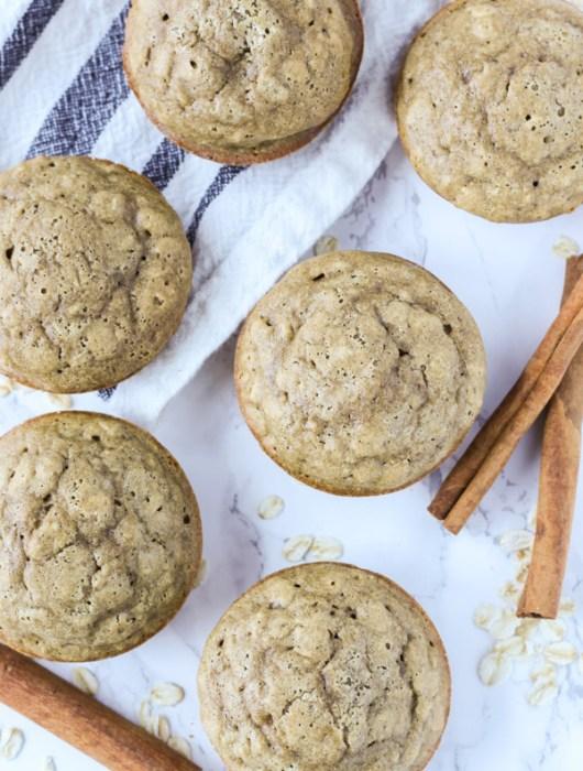 Overhead shot of cinnamon oat muffins with cinnamon sticks
