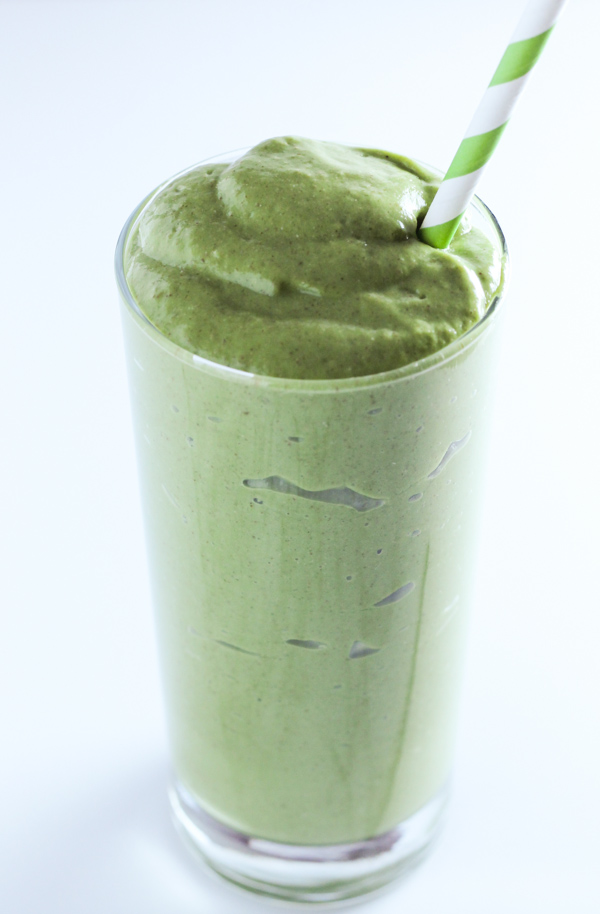 Tall skinny glass filled with green smoothie and a green and white striped straw.