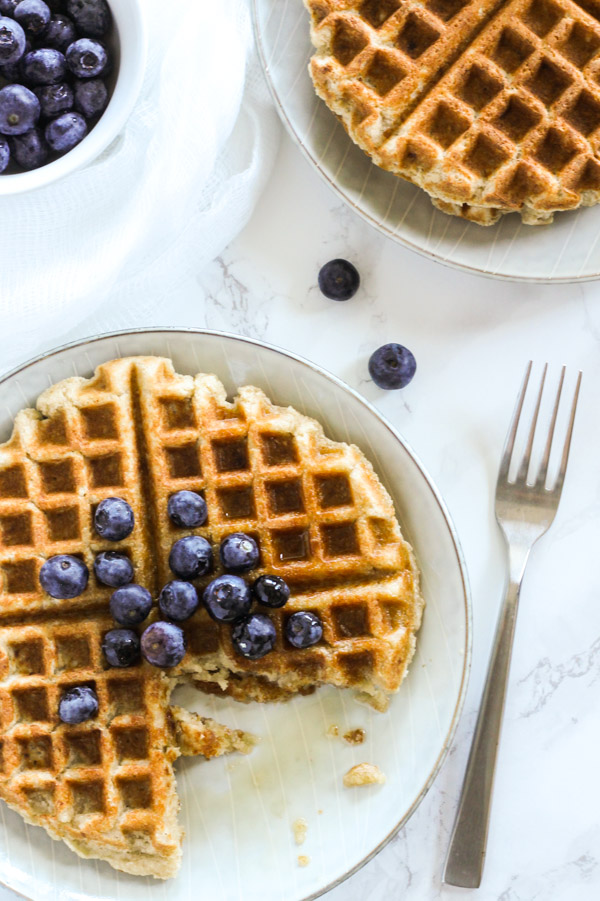Overhead view of partially eaten waffle with blueberries