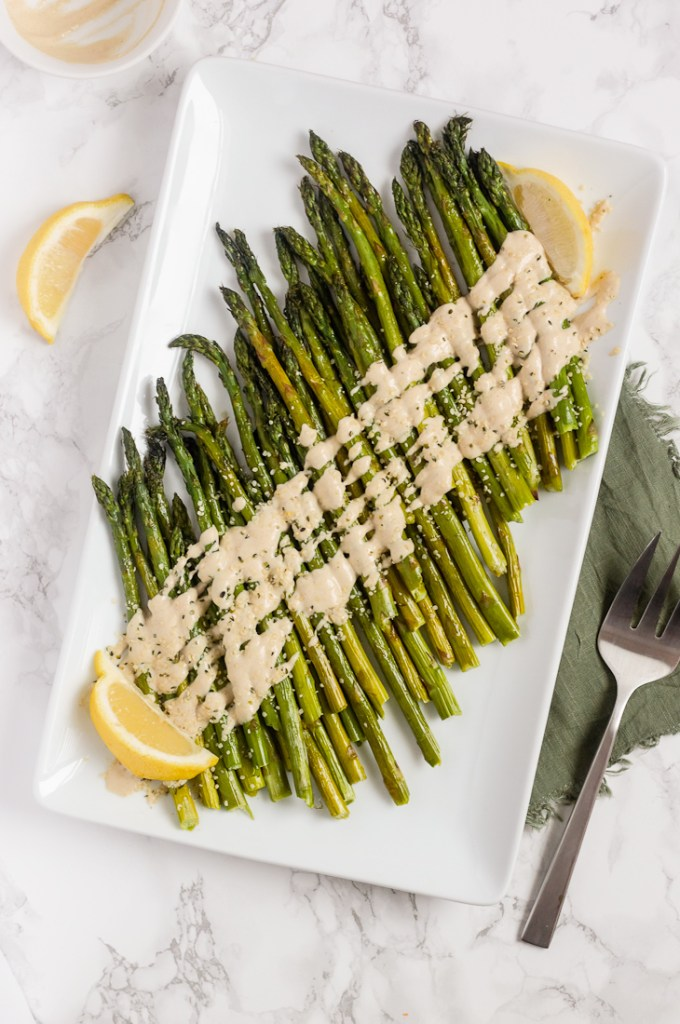 overhead view of roasted asparagus with tahini on white serving plate