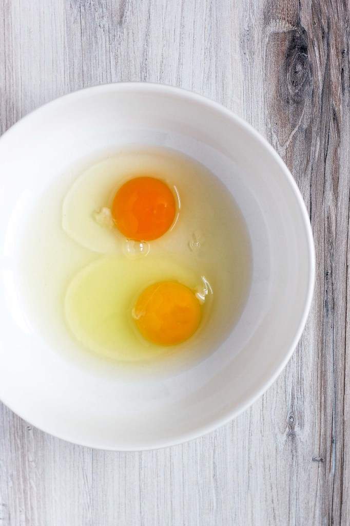 2 cracked eggs in a white bowl - one is brighter orange