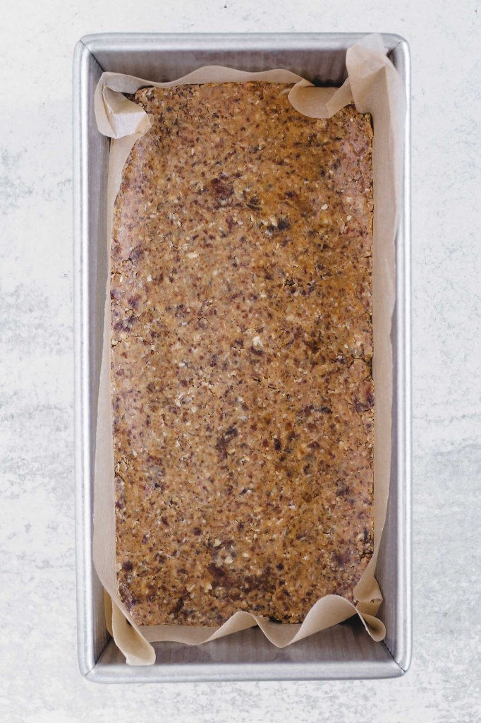 "overhead view of blended ingredients ""dough"" pressed down in bottom of loaf pan"