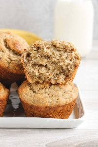 side view of banana muffins stacked two high with top one split open to see the inside of the muffin