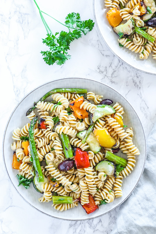 overhead view of grilled vegetable pasta salad in single serve round plate