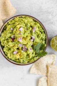 overhead view of guacamole in a serving bowl with chips sprinkled on the side