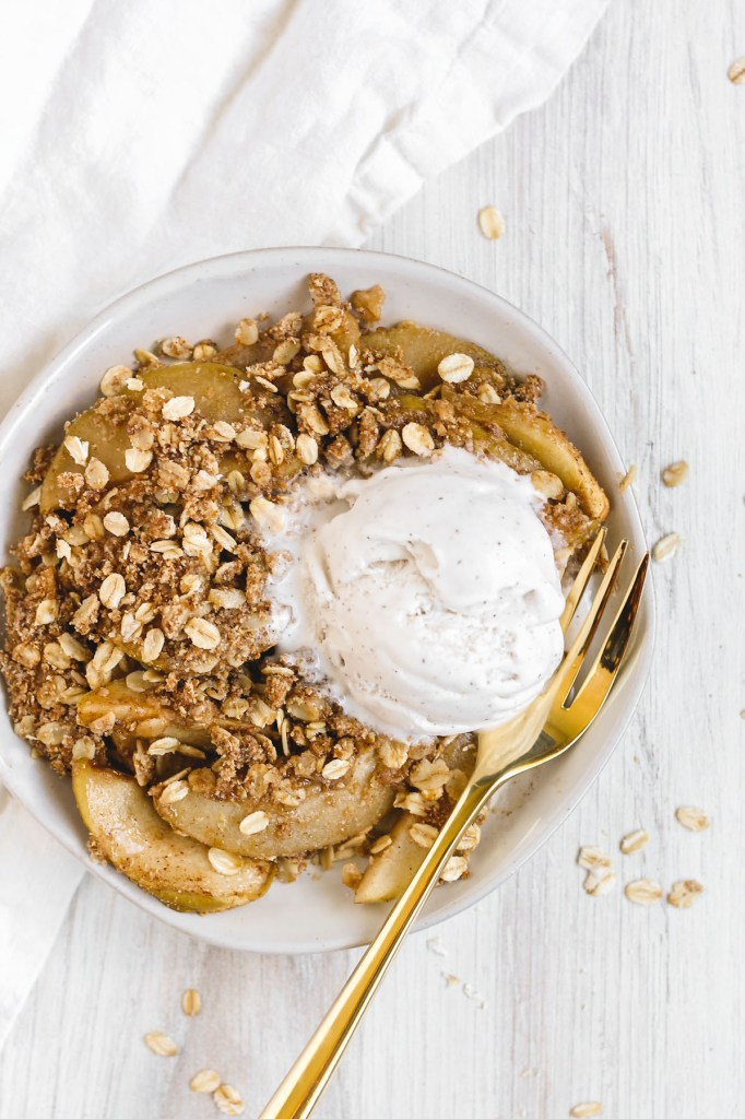 close up view of single serving of apple crisp with melting vanilla ice cream