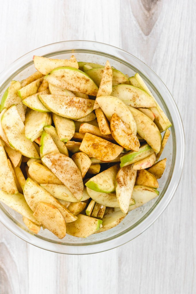 bowl of sliced apples with cinnamon sprinkled all over