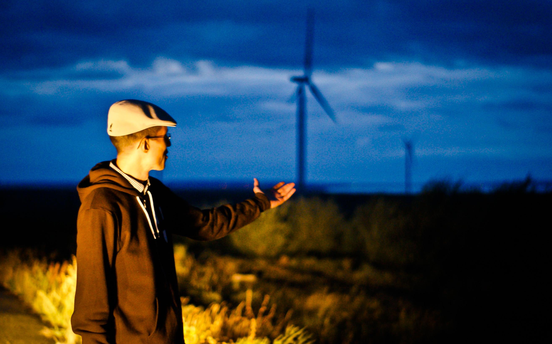 Zachary Shahan at a wind farm. Credit: Mariia Khandus / Zachary Shahan
