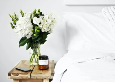 white flowers on tidy nightstand next to white bed