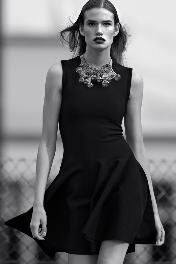 woman in black a-line dress with statement necklace