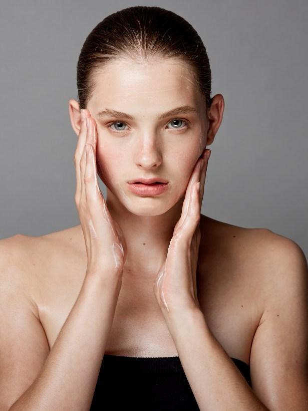 girl putting on facial moisturizer