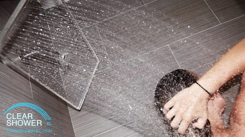 Girl showering with waterfall showerhead in grey bathroom