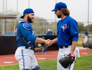 Toronto Blue Jays starting pitcher R.A. Dickey, right, shakes hands with Blue Jays catcher Russell Martin, left, after pitching in the bullpen during baseball spring training in Dunedin, Fla., Wednesday, Feb. 25, 2015. (AP Photo/the Canadian Press, Nathan Denette)