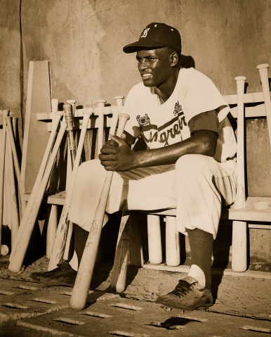 Roberto Clemente sits in the dugout while playing for the Cangrejeros de Santurce.