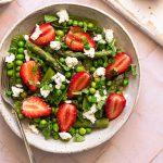 fond rose pâle avec assiette blanche contenant une salade de roquette, quinoa, fraises, petits pois et asperges avec des morceaux de fromage de chèvre frais et de la menthe