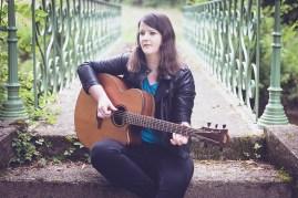 Clem jouant de la guitare assise sur les marches d'un pont