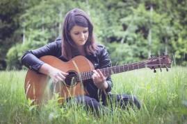 Clem jouant de la guitare assise dans l'herbe