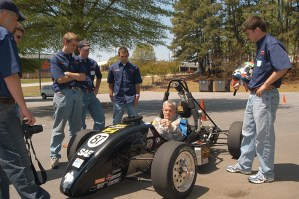 Always up for a challenge, Barker straps in to the Formula SAE car built by students.