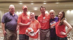 Rion Holcombe (center), who recently was accepted into the ClemsonLIFE programs, and his family with President Clements and Coach Swinney.