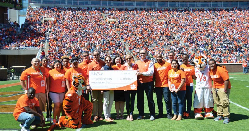 Clemson Trustee Mark Richardson and his wife, Kathryn, present a check at the Spring Game representing their $1 million gift in support of Emerging Scholars students.