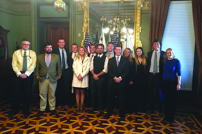 Clemson University economics students gather in front of the flags where cabinet members are sworn in.