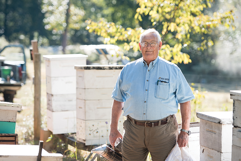 Buddy May amidst his many beehives on May Farms. The smoker in his hand is used to produce a kind of fire alarm in the hive, keeping the bees busy while May checks up on them.